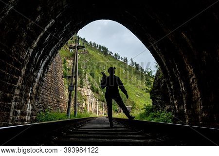 Russia, Angasolka - July 2020: Silhouette Of A Photographer In A Tunnel Of Circum Baikal Railway