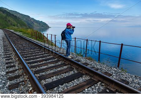 Russia, Angasolka - July 2020: Photographer In Blue Jacket Taking Pictures Of Baikal Lake