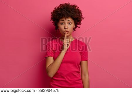 Photo Of Shocked Surprised Dark Skinned Woman Keeps Index Finger Over Lips, Makes Silence Gesture, T