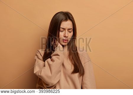 Horizontal Shot Of Displeased Brunette Woman Touches Neck, Feels Painful Feelings, Has Back Or Spine