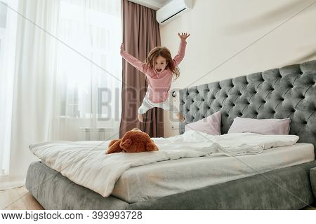 A Cute Little Happy Girl Jumping Down Like A Star On Her Teddybear Barefoot On A Bed In A Huge Bedro