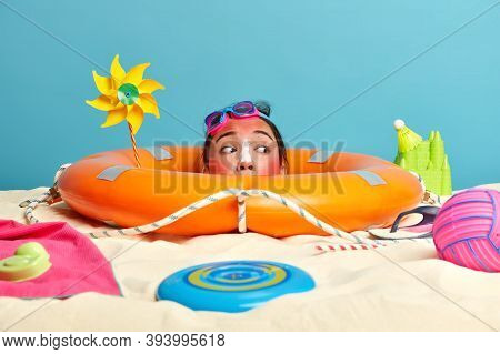 People, Summer, Relaxation, Holiday Concept. Curious Woman Buried In Sand, Looks From Inflated Lifeb