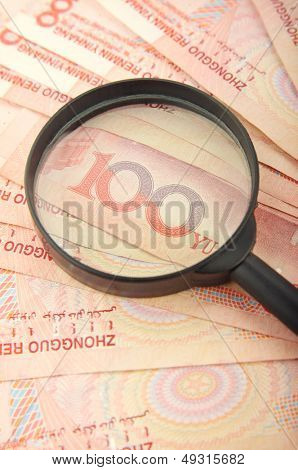 magnifying glass lying on several rmb  bills