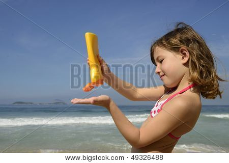 child applying sunscreen on the beach during summer vacation