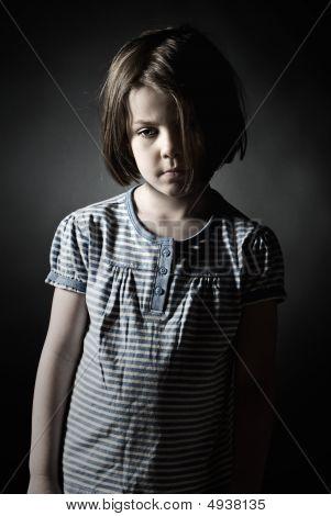 Low Key Shot Of A Sad Little Girl Against Grey Background