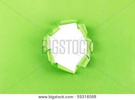 Ripped hole in green paper isolated over a white background