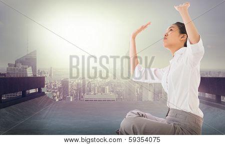 Businesswoman sitting cross legged pushing up against cityscape on the horizon