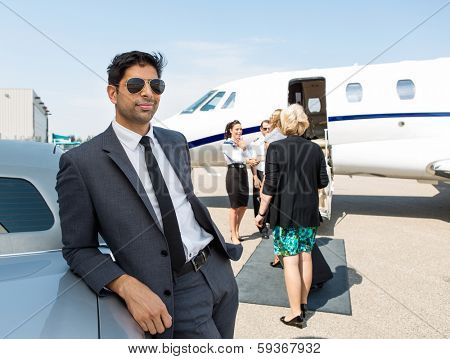 Confident businessman leaning on car with airhostess and pilot greeting business people against private jet