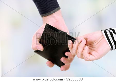 Pickpocket are stealing wallet,  close up, on light background