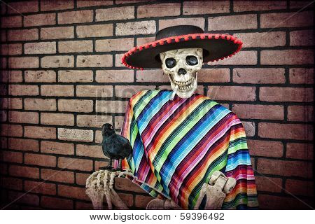 Latino skeleton sitting against a brick wall having a smoke with his trusty pet crow. poster