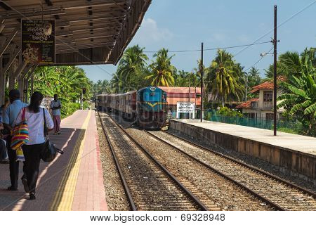 HIKKADUWA, SRI LANKA - MARCH 12, 2014: Train approaching Hikkaduwa train station. Trains are very cheap and poorly maintained but it's the best option to witness a bit of everyday local life.