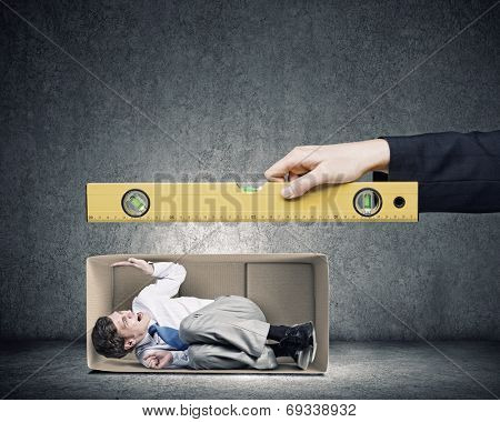 Businessman in the box and hand with measure tool
