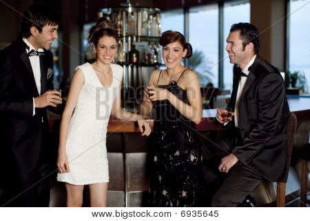 Two Couples At Bar Drinking And Flirting