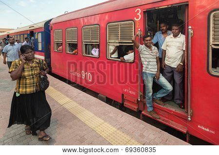 COLOMBO, SRI LANKA - FEBRUARY 22, 2014: Commuters in train at Colombo station. Trains are very cheap and poorly maintained but it's the best option to witness a bit of everyday local life.
