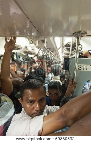 HIKKADUWA, SRI LANKA - FEBRUARY 22, 2014: Crowded commuter train to Colombo. Trains are very cheap and poorly maintained but it's the best option to witness a bit of everyday local life.