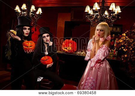 Halloween concept: sexy ladies vampire with halloween pumpkins assailing blond girl
