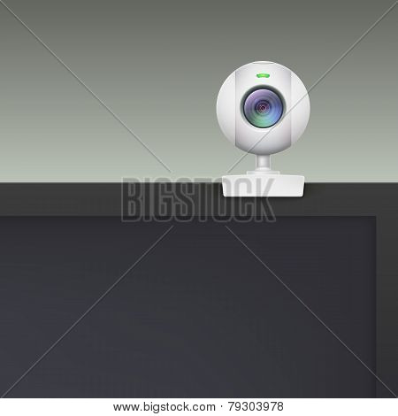 Webcam of white plastic standing on the monitor.