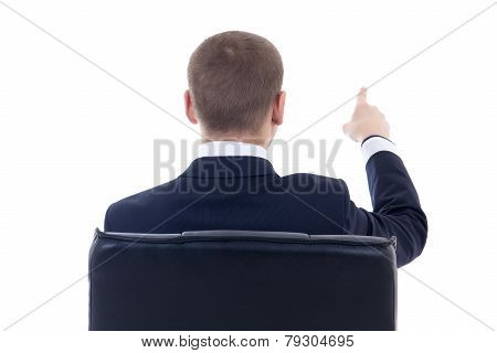 Back View Of Business Man Sitting On Office Chair And Pointing At Something Isolated On White