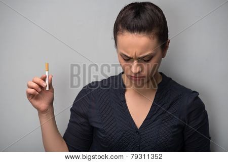 Closeup of young attractive Caucasian woman determined girl holding cigarette looking down. Quit smoking. Studio shot isolated on grey. Addiction concept poster