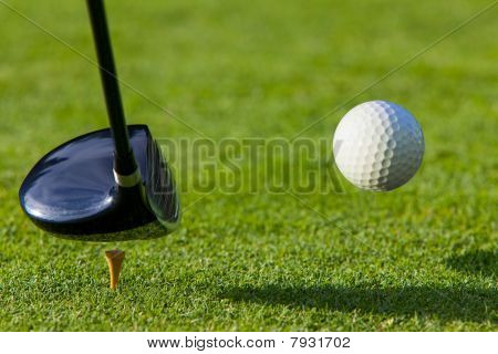 Golf ball hit off the tee with driver on golf course