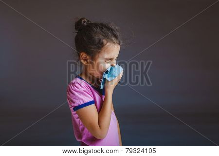 girl blowing his nose into a handkerchief isolated