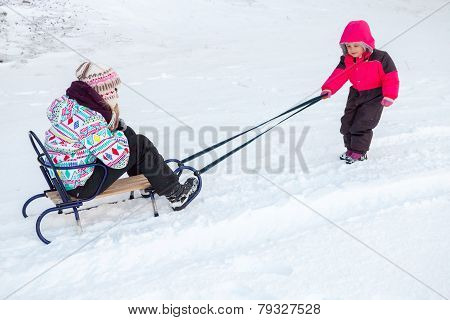 Little Baby Girl In Pink Pulling A Sled On Snowy Road