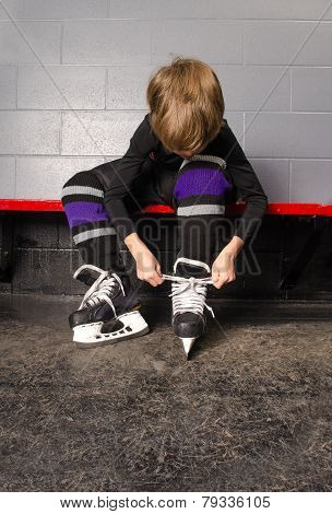 Boy Tying Hockey Skates In Dressing Room