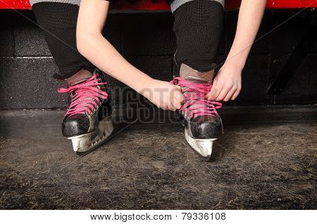 A Girl Tying Ice Hockey Skates In Dressing Room