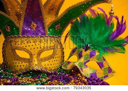 A festive, colorful group of mardi gras or carnivale mask on a yellow background.  Venetian masks.