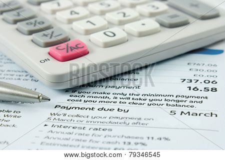 Close Up Of A Calculator And A Pen Sitting On A Bank Statement