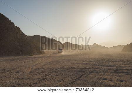 Off Road Vehicle Traveling Through Arid Desert Landscape