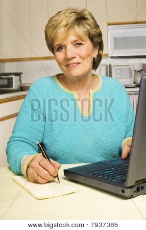 Woman Writes A Note While Using A Laptop.
