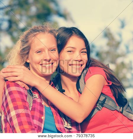 Girlfriends. Happy girls young women hiking portrait of smiling multiracial friends having fun together on hike in forest enjoying active healthy outdoors lifestyle. Asian and Caucasian woman outside.