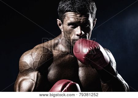 Strong Muscular Boxer In Red Boxing Gloves. A Man In A Boxing Stand