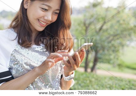 Beautiful Woman Playing And Touching On Smart Phone Screen In Outdoor Of Home Garden Field