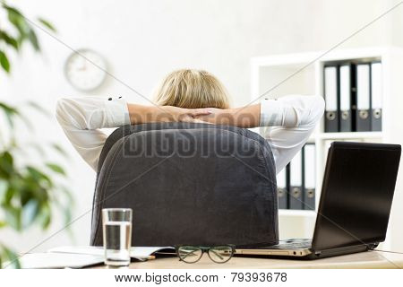 Woman relaxing in office sitting back in chair with hands behind neck
