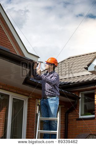 Carpenter Standing On High Ladder And Repairing House Roof