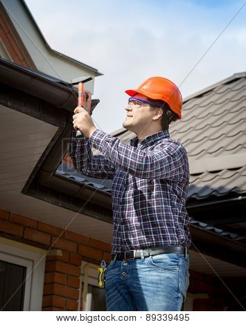 Young Handyman Repairing House Roof With Nails And Hammer