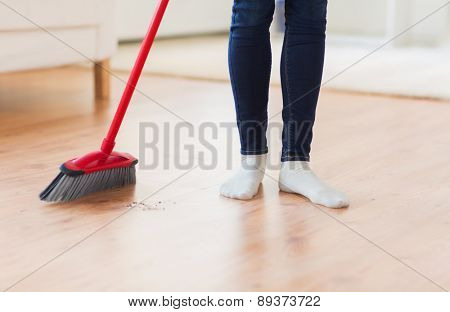 people, housework, cleaning and housekeeping concept - close up of woman legs with broom sweeping floor at home poster