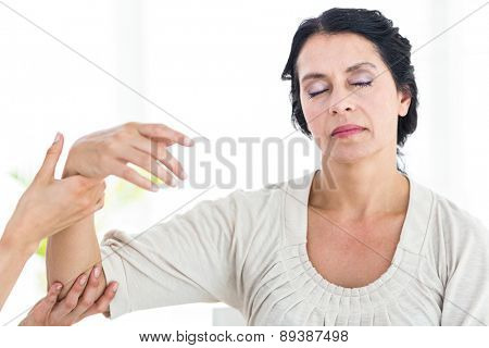 Therapist holding her patients arm on white background