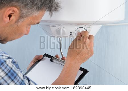 Plumber Adjusting Temperature Of Electric Boiler