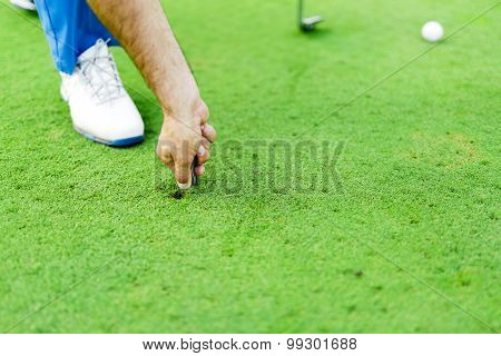 Golf Player Repairing Divot