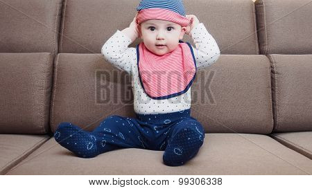 Caucasian baby boy weared bib sitting on braun sofa at home poster