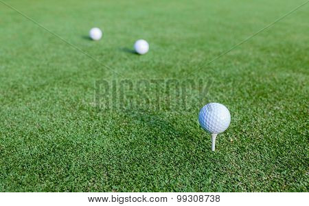 Golf Ball And Tee On Green Grass During Training At Golf Club.