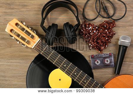 Music recording scene with classical guitar, vinyl record, microphone, cassette and headphones on wooden background poster