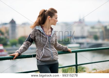 Woman Runner With Headphones In Profile, Up Against Guardrail
