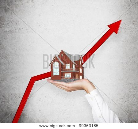 A Hand Is Holding A House. A Huge Red Arrows Rocketing As Concept Of Rising Real Estate Market.