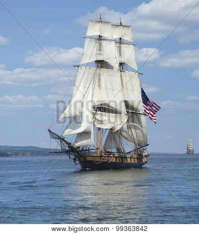 A tall ship known as a brigantine sails on blue water with an American flag flying poster
