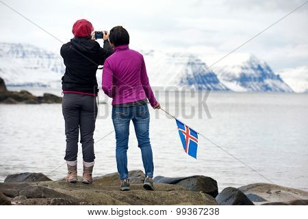 Girlfriends travelling together enjoying the scenery taking photos from the viewpoint in the westfjords, iceland. independent self drive holidays