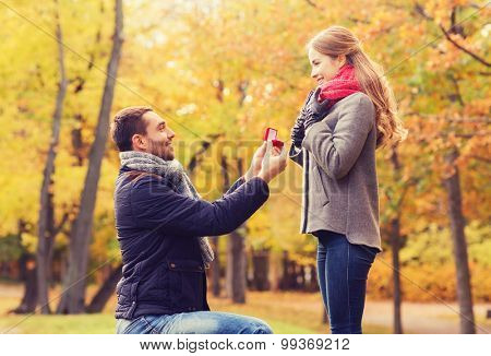 love, family, autumn and people concept - smiling couple with engagement ring in small red gift box outdoors